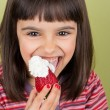 Little girl eating strawberry with cream — Stock Photo