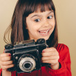 Funny little retro photographer girl — Stock Photo