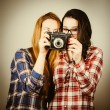 Hipster girls using an old camera — Stock Photo