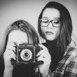 B&W portrait of hipster girls using an old camera — Stock Photo