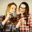 Funny hipster girls taking pictures with an old camera — Stock Photo