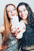 Beautiful girls making a self portrait with mobile — Stock Photo