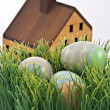 Easter Eggs Hiding in Tall Grass with Toy House - Stock Photo