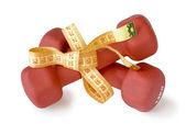 Red dumbbells tied measuring tape — Stockfoto