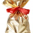 Golden gift bag with a red bow — Stock Photo