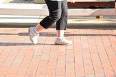Legs of woman walking slowly on the footpath — Stock Photo