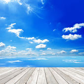 Wooden deck with blue sea and sky background — Stock Photo