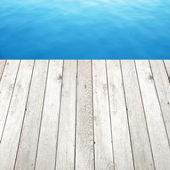 Wood plank on blue water background — Stock Photo