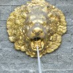 Golden lion head sculpture on stone wall — Stock Photo #44530789