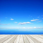 Wooden pier on blue sea and sky background — Stock Photo