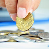 Fingers picking up a coin - one Australian dollar (AUD) — Stock Photo