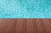 Brown wood plank over swimming pool — Zdjęcie stockowe