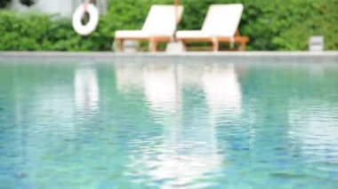 Rippled water in swimming pool with beach chairs & green plant background — 图库视频影像