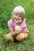 The happy child sits on meadow with flower in hand. — Stock Photo