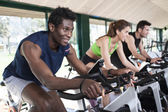 Tres amigos están en una clase de spinning en el gimnasio — Foto de Stock