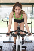 Young woman riding an exercise bike — Stock Photo
