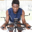 Young black mriding exercise bike — Stock Photo #23684411