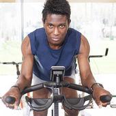 Young black man riding an exercise bike — Stock Photo