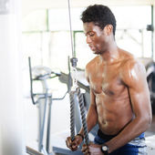 Muscled young black man working hard in the gym — Stock Photo