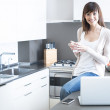 Beautiful lady using a laptop at kitchen — Stock Photo