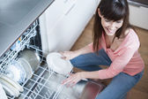 Middle aged girl in the kitchen using diswasher — Stock Photo