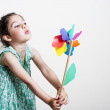 Beautiful girl blowing a plastic windmill — Stock Photo