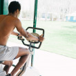 Black mduring stationary bike session at gym — Stock Photo #28484811