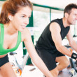Athletes using stationary bicycle in gym — Stock Photo #28484945