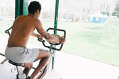 Black man during a stationary bike session at gym — Stock Photo