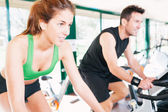 Athletes using the stationary bicycle in a gym — Stock Photo