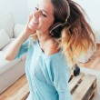 Happy girl dancing at home while listen music with headphones — Stock Photo