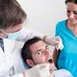 Dental surgery. There is a dentist, his assistant and the patient — ストック写真
