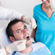 Dental surgery. There is a dentist, his assistant and the patient — Stok fotoğraf
