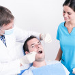 Dental surgery. There is a dentist, his assistant and the patient — Stock Photo #32419843