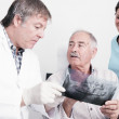 Dental Clinic. An elderly retired gentleman, discussing with his dentist radiography (x-ray) results — Stock Photo