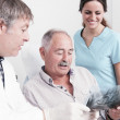 Dental Clinic. elderly retired gentleman, discussing with his dentist radiography (x-ray) results — Stock Photo #32441453