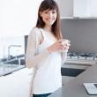 A beautiful woman in her kitchen during her breakfast. She is using her laptop. — Stock Photo