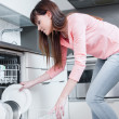 A beautiful woman using a dishwasher in a modern kitchen. domestic appliance — Stock Photo