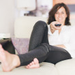 Womusing TV remote while resting on sofat home — Stock Photo #34134511