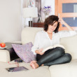 Woman reading a book while resting on the sofa — Stock Photo