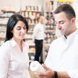 Pharmaceutical giving advice on medication to one customer — Stock Photo
