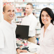 Smiling pharmacist with two customers in a pharmacy — Stock Photo