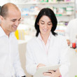 Pharmaceutical giving advice on medication to a customer — Stock Photo