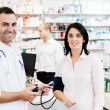 Pharmacist check woman blood pressure — Stock Photo