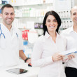 Pharmaceutical attending two customers — Stock Photo