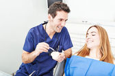 Dentist and the patient commenting about medical treatment — Stock Photo