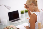 Blonde woman reading in her worksapce. Lateral view — Stock Photo