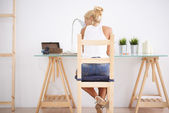 Blonde woman using her laptop in her worksapce. View from behind — Stock Photo