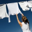 Girl, blue sky and white laundry — Stock Photo