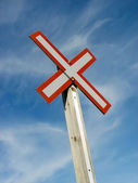 Railroad crossing sign on a blue sky background — Stock Photo